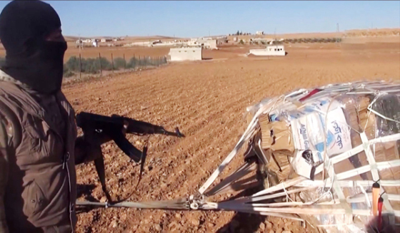 An image grab taken from a video released on October 21, 2014, by Aamaq News, a Youtube channel which posts videos from the areas under the Islamic State (IS) group's control, purportedly shows an IS militant pointing towards a crate attached to a parachute near the town of Ain al-Arab, known by the Kurds as Kobane, on the Syria-Turkey border. A US military airdrop of weapons meant for Kurdish fighters fell into the hands of their jihadist foes near the Syrian battleground town of Kobane, the Syrian Observatory for Human Rights said. AFP PHOTO / HO / AAMAQ NEWS == RESTRICTED TO EDITORIAL USE - NO MARKETING NO ADVERTISING CAMPAIGNS - DISTRIBUTED AS A SERVICE TO CLIENTS FROM ALTERNATIVE SOURCES, AFP IS NOT RESPONSIBLE FOR ANY DIGITAL ALTERATIONS TO THE PICTURE'S EDITORIAL CONTENT, DATE AND LOCATION WHICH CANNOT BE INDEPENDENTLY VERIFIED ==