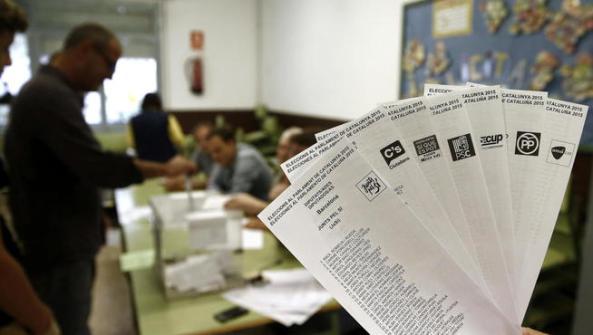 gra005-barcelona-27-09-2015-una-persona-muestra-las-papeletas-de-los-diferentes-partidos-que-concurren-a-las-elecciones-al-parlamento-catalan-que-se-celebran-hoy-en-cataluna-mientras-una-persona-de